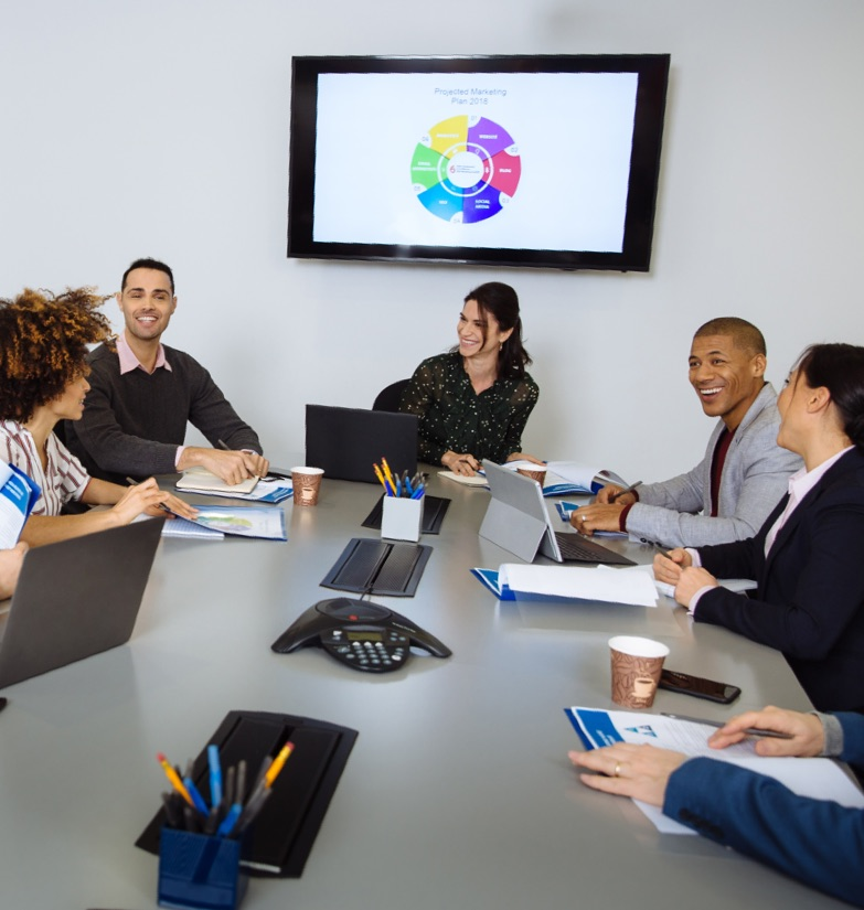 Business meeting with presentation displayed on mounted screen in conference room for rent in NYC, fit up to 20 people and reserve online or on the phone.