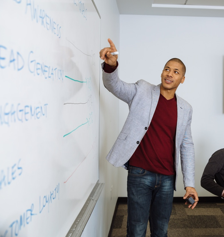 Businessman Professional conducting training class in rented conference room with white board presentation in New York City.