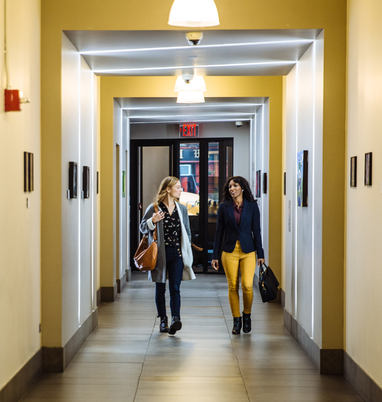 Two business women walking through brightly lit hallway in Inwood co-working location in NYC for lease.