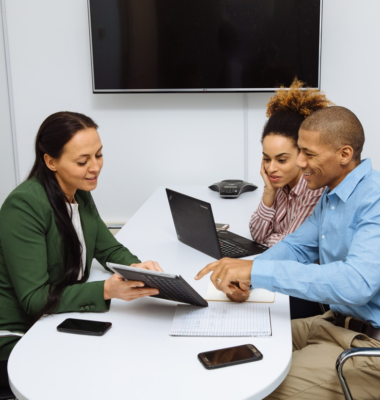 Businesswoman consulting with two clients showing options on smart tablet with television in the background at WorkSpace Offices with private phone room and conference rooms available for all tenants.