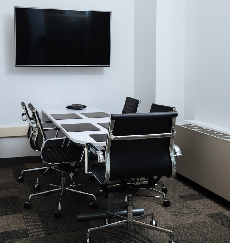 Inwood Conference room with abundant seating and mounted television for presentations for rent with onsite management in Uptown NYC.