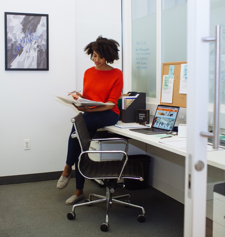 Businesswoman Woman reviewing notes sat atop desk inin a Flexible Office room for rent in NYC.