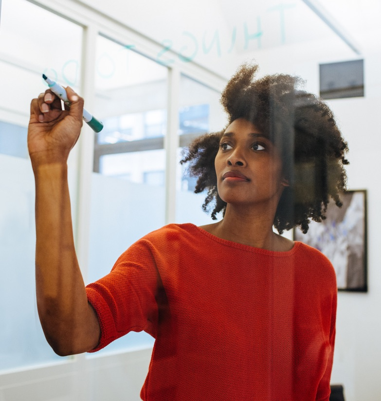 Businesswoman making notes on glass wall in Flexible Office space for rent in Hudson Square.