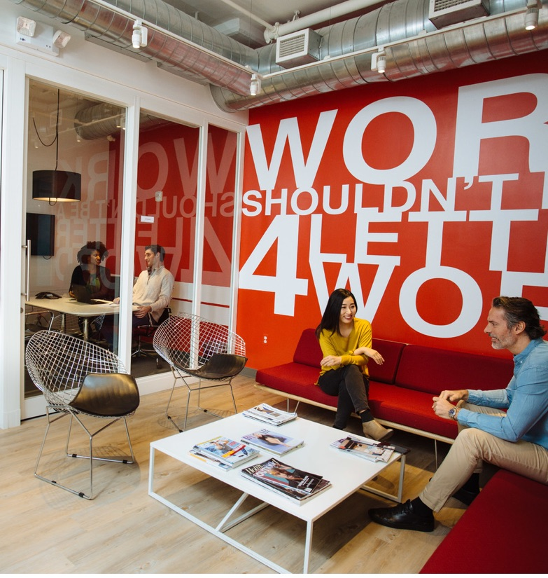 Business persons people sitting in shared seating area with red accent wall and glass office in the background in SoHo, NY in our shared coworking space for rent.
