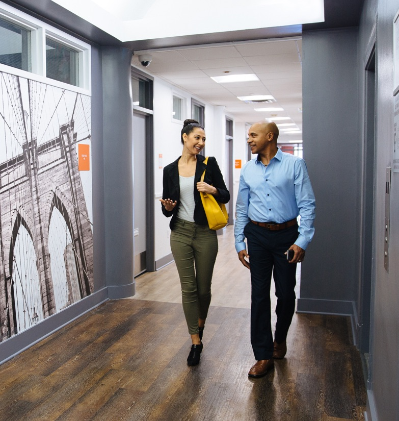 Two business persons people walking and chatting through a renovated hallway at WorkSpace SoHo in downtown NYC as they approach the elevator.