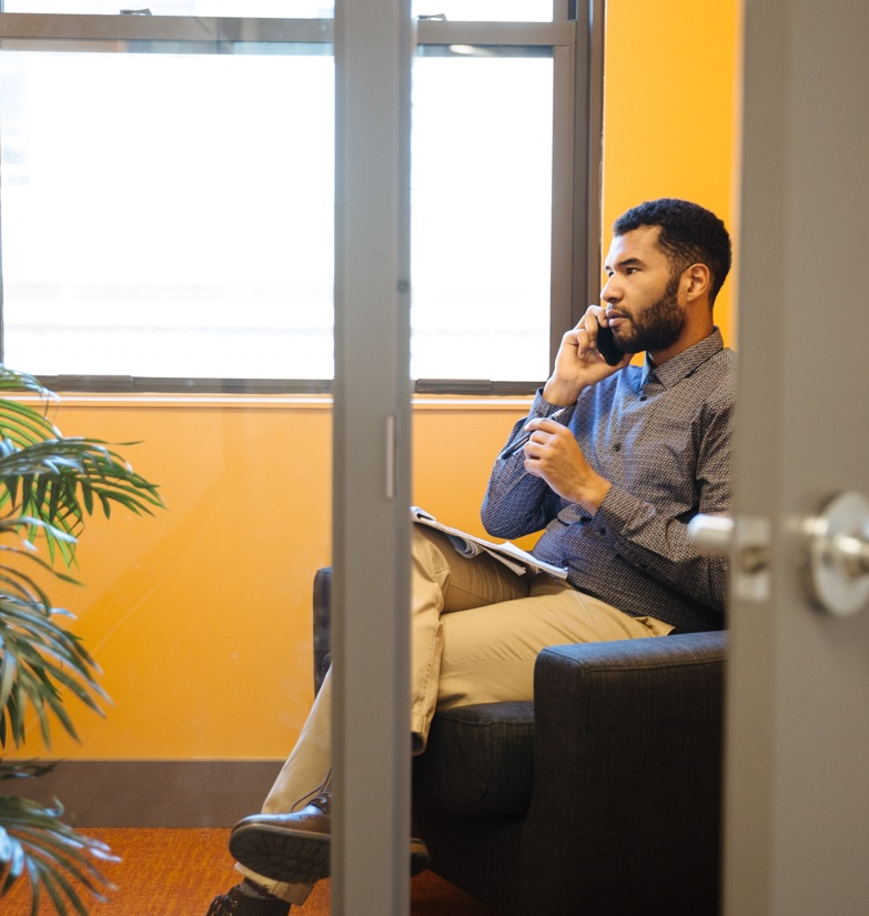 Professional person conducting phone call in private glass phone booth available to all office tenants at WorkSpace Offices with soundproof walls and abundant light.