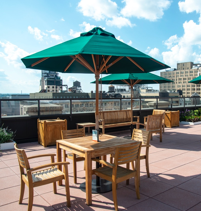 View from rooftop terrace accessible by all tenants with an office lease at WorkSpace Offices SoHo with large green umbrellas providing shade from the beautiful bright sun.