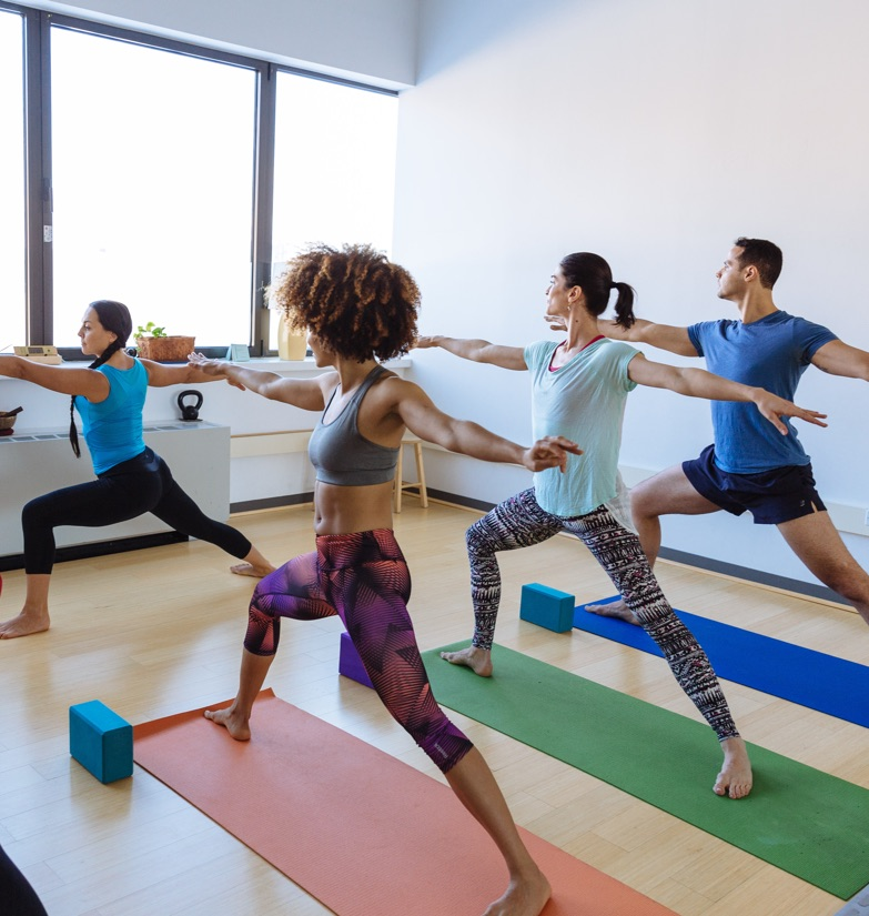 Yoga instructor conducting class in brightly lit convertible studio for rent at WorkSpace Offices.