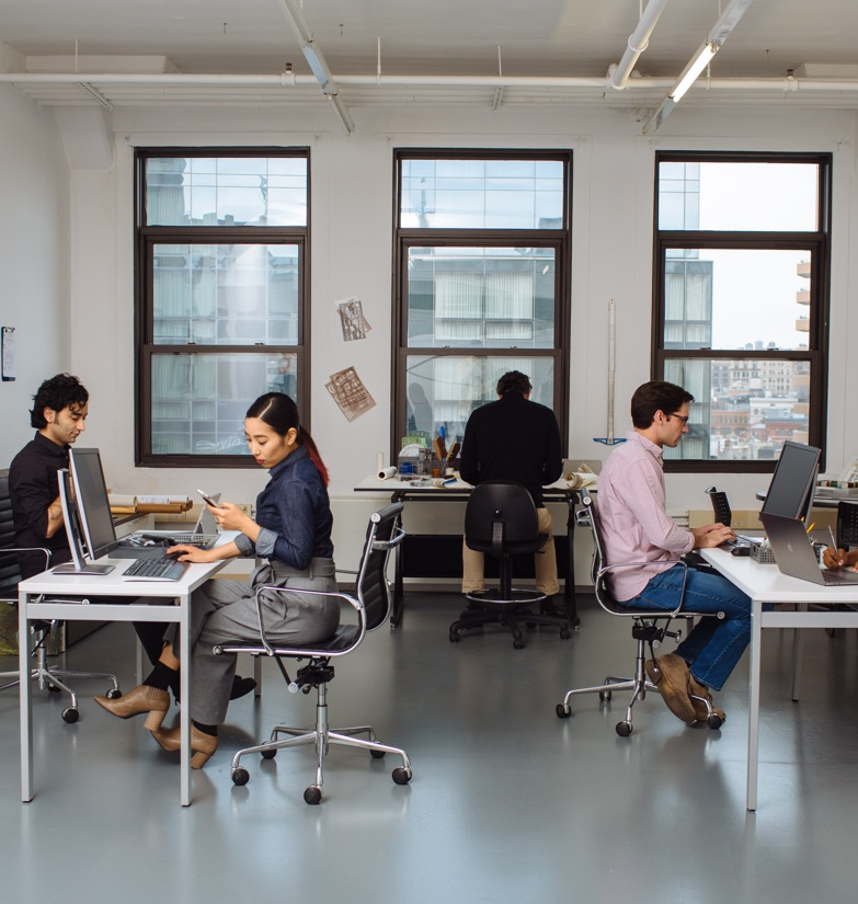 Employees seated at shared desk space in Growth Suite for rent in New York City.