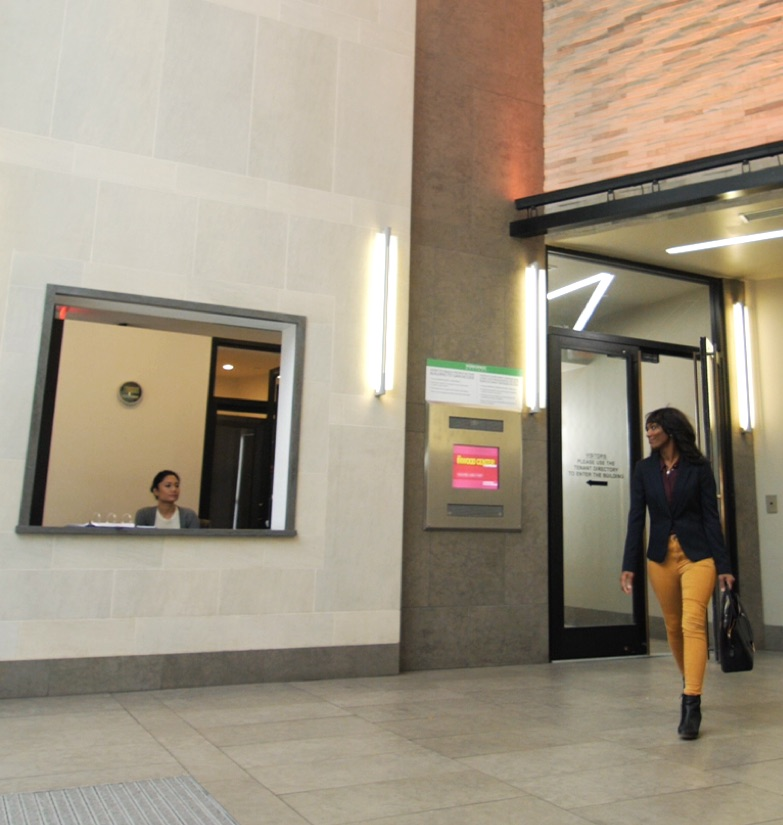 Businesswoman walking passed reception in Manhattan co-working location with available desks for lease.