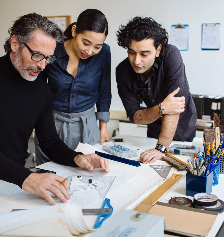 3 architects discuss blueprints and plans while refining measurements at drafting table in private suite for rent.