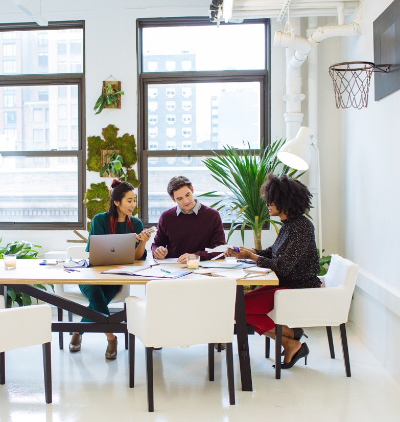 Business associates seated at executive table in Startup Suite available for short-term lease with large windows and basketball hoop on far right wall in Manhattan.