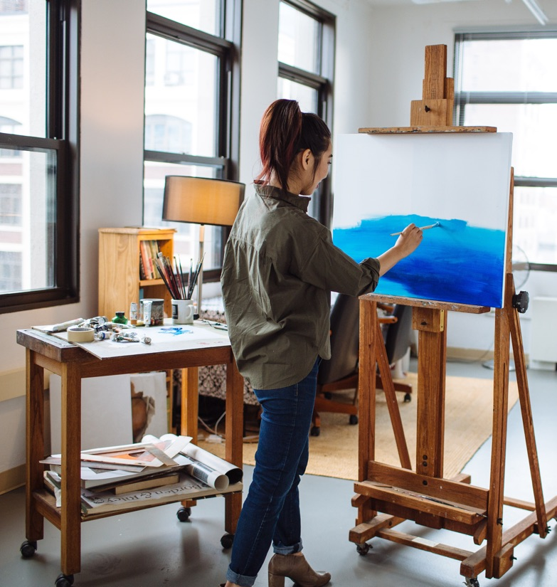 Artist painting canvas on easel in flexible Startup Suite surrounded by art supplies in brightly lit space for rent in Manhattan.