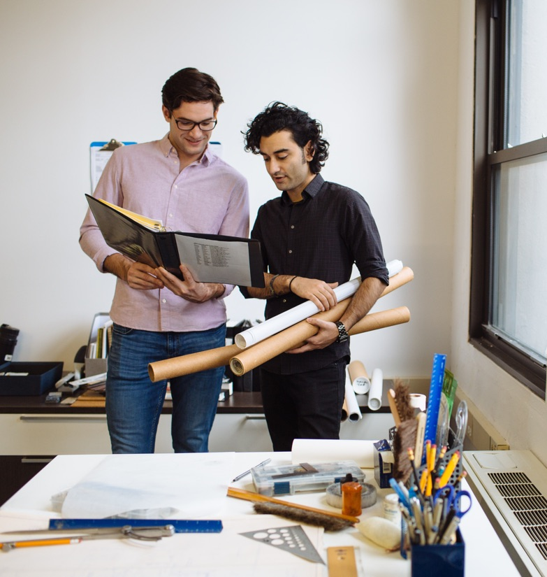 Two professionals discussing plans drafts in private, flexible office space in a WorkSpace Offices Startup Suite in New York, NY.e with blueprints in hand.